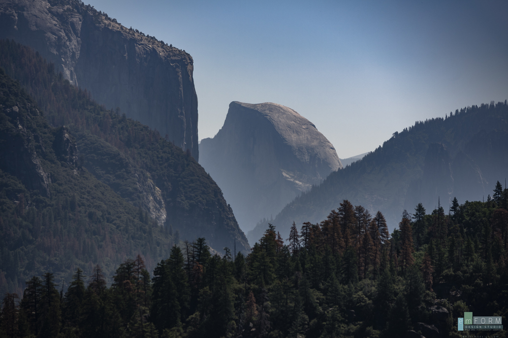 A light blanket of smoke drifting through Yosemite valley from a nearby wildfire, adds a little drama to this late morning view of Half Dome.