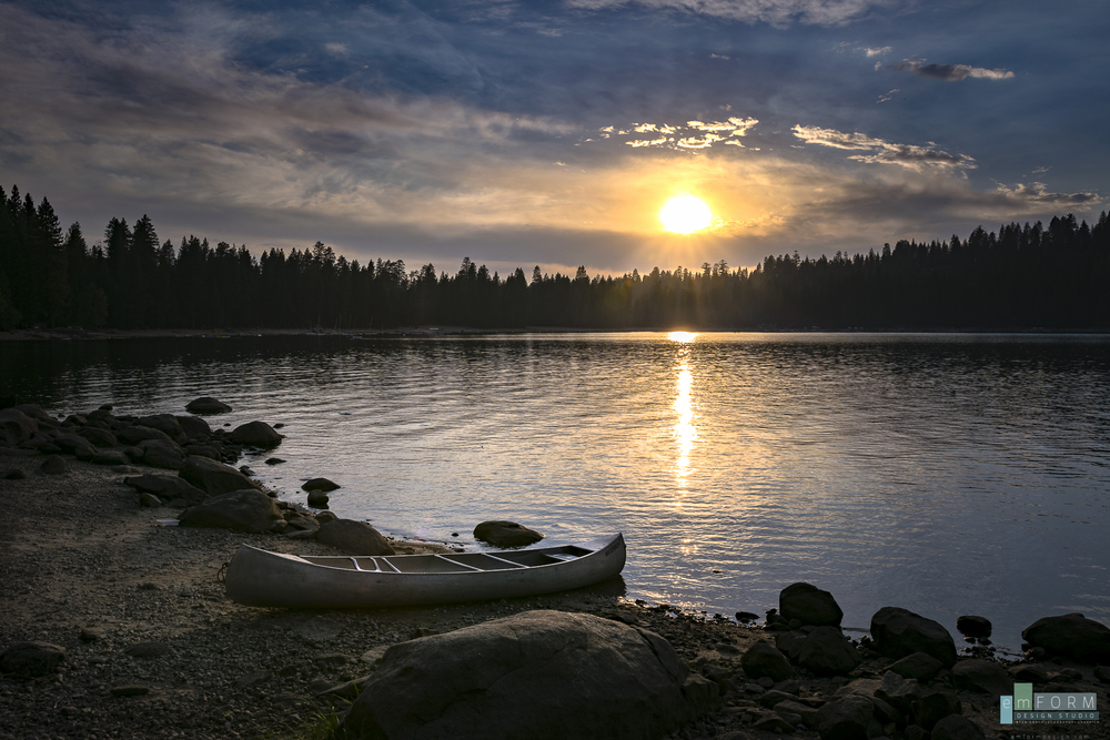A lone canoe rests on the shore of Pinecrest lake at sunset.  ISO100 -18mm -F9 -1/400
