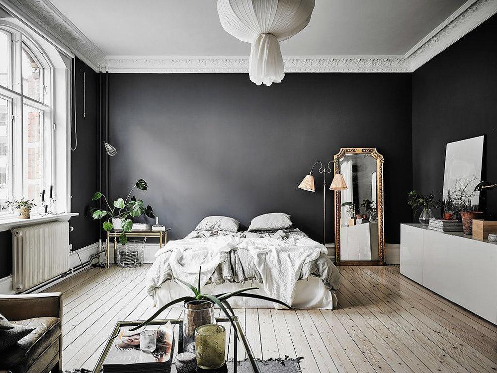 moody-bedroom-gilt-mirror-black-walls-linen-bed-light-wood-floors-parisian-apartment