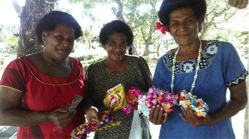 Fijian women holding their handcrafted purses made from strips of plastic snack packaging.