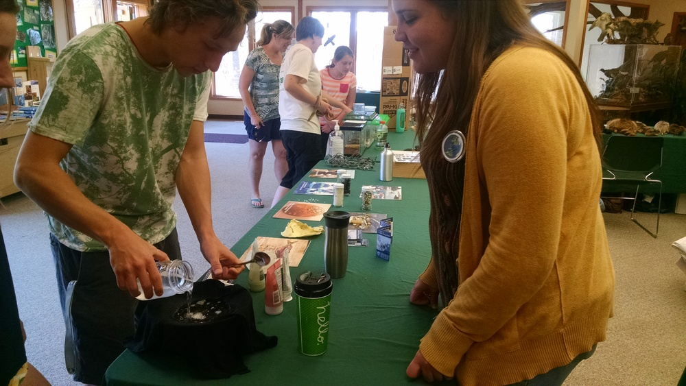 Kayla working with volunteer to carry out the microbead demonstration.