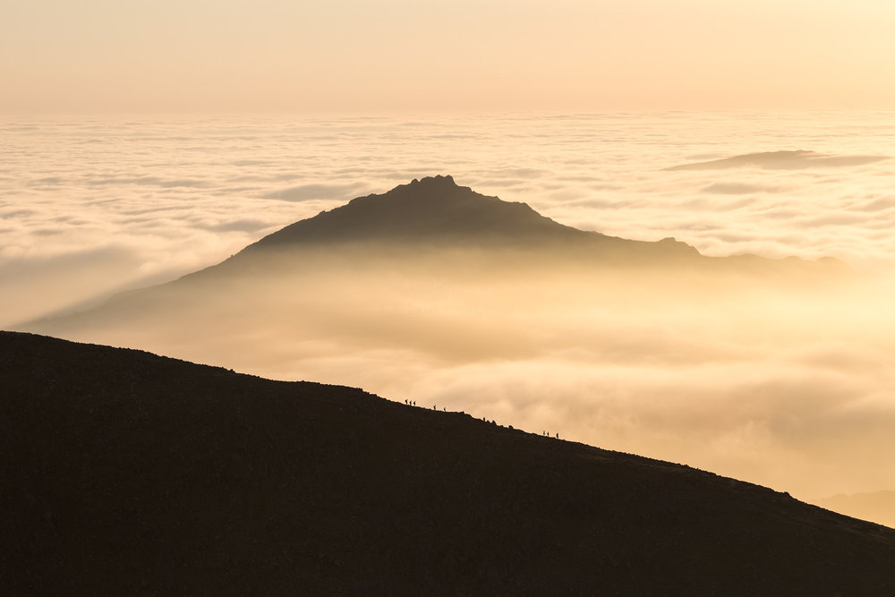 Walking the sunset skyline through the clouds. Dow Crag . Buy as a print