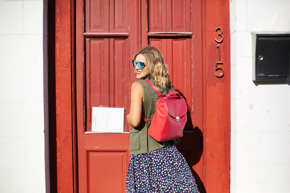 polka dot navy dress:J.Crew: Sneakers: Red backpack:Green vest-5.jpg
