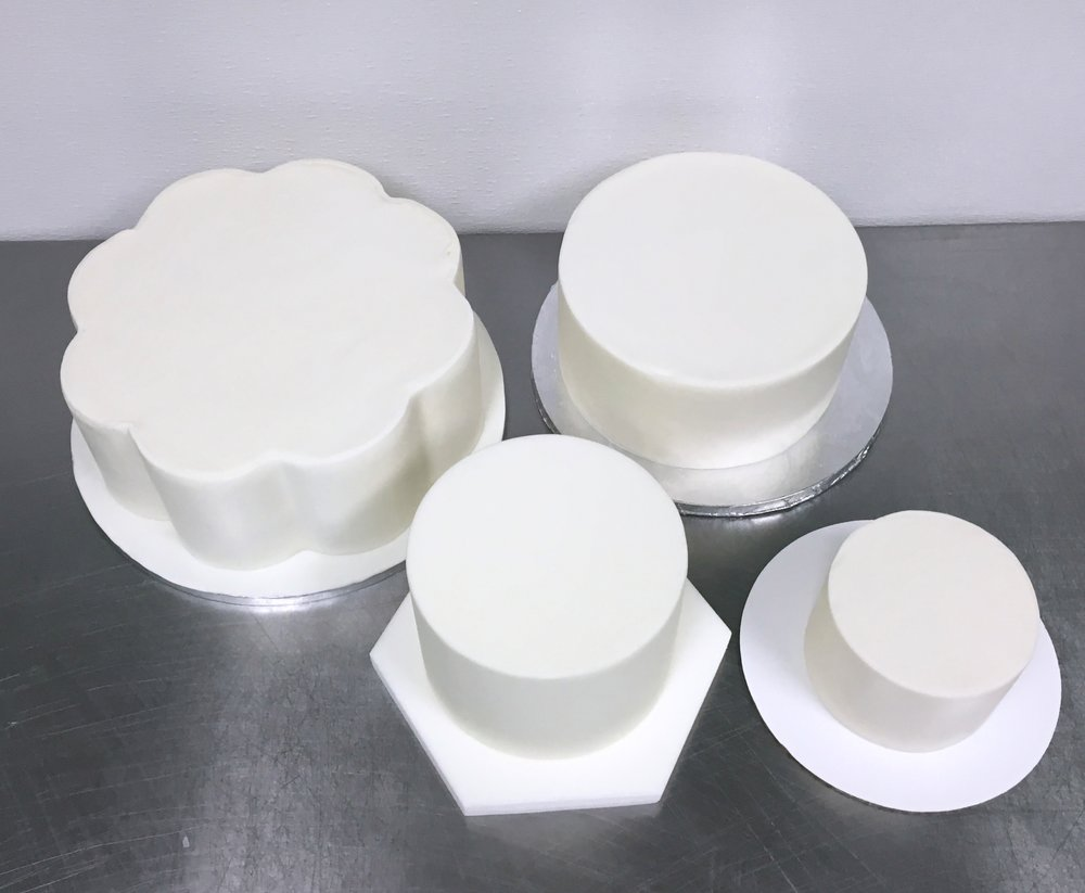 Smooth, white, fondant-covered wedding cakes ready to be stacked and decorated