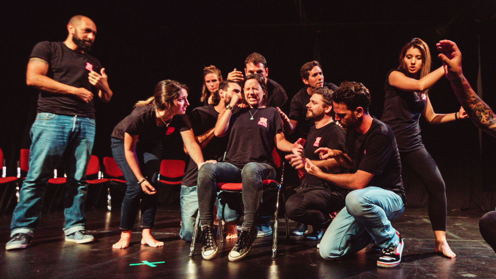 A group of actors, dressed in blue jeans and black tshirts, in the middle of a dynamic scene