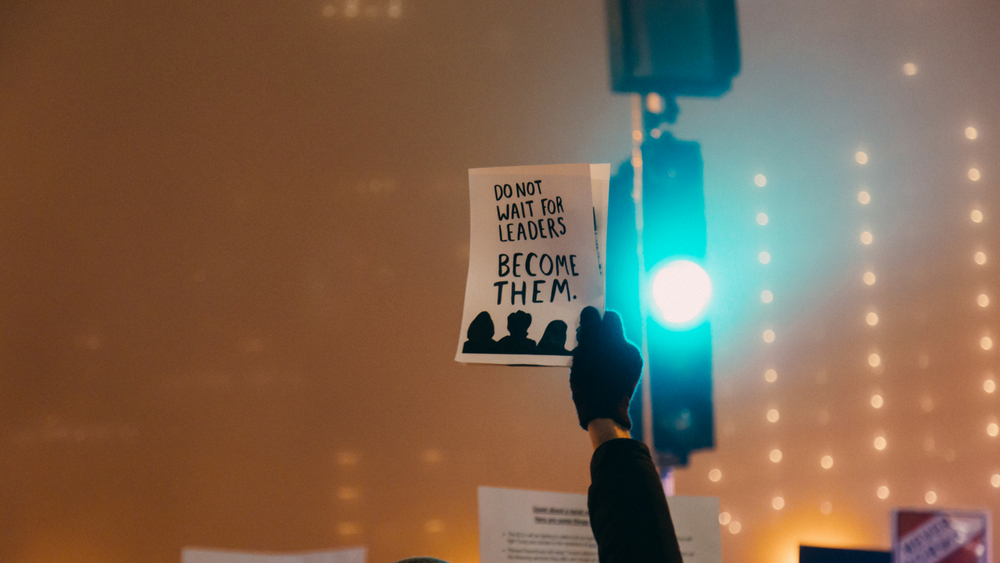 "A protest sign held in front of a street light reading ""Do not wait for leaders. Become them."""
