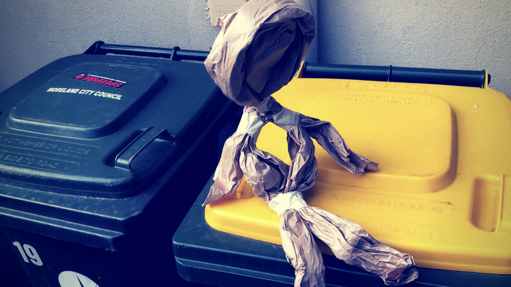 A small puppet made from scrunched up brown paper, sitting on top of two bins