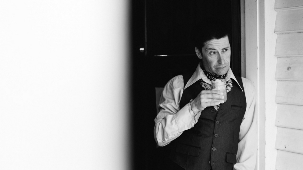 A man in a waistcoat and shirt holding a drink, looking off into the distance from a doorway