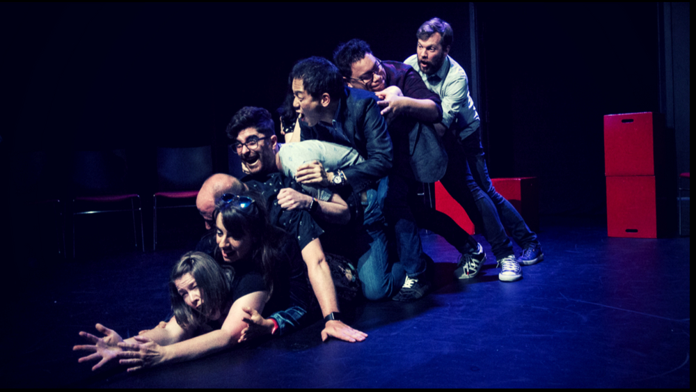 A group of actors piled on top of each other, excited and yelling