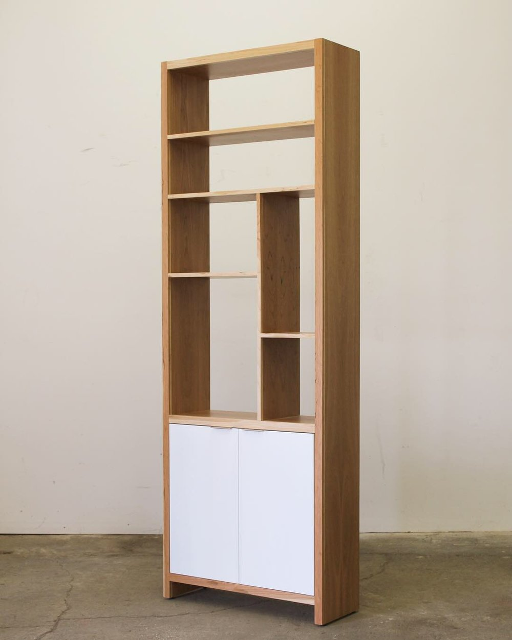 Cherry Asymmetrical Shelving Unit   This shelving unit features cherry veneer with hard wood edge taping and a white cabinet below. It measures 30'' W x 12'' D x 94'' H.  $2500
