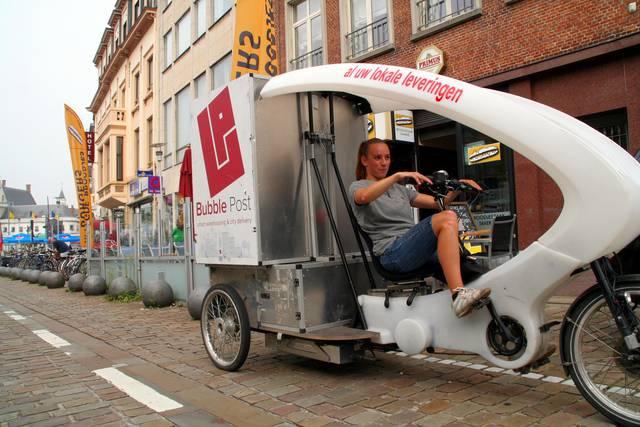 Kristof Hermans van broodjeszaak Winny's laat zijn broodjes bij bedrijven leveren door de fietsende pakjesdienst. - Joris Vergauwen