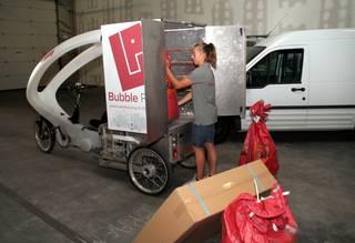 In het magazijn van Bubble Post vlakbij de E17 zetten vrachtwagens de goederen af, die vervolgens in de cargofiets worden geladen. - Vergauwen