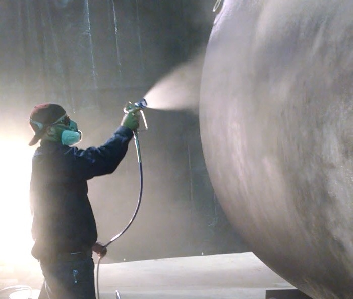 Applying NEETcoat® with an airless sprayer to a fiberglass tank prototype.