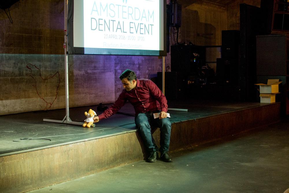 Dagvoorzitter Sinan Cihangir, die later op de dag voor lastige patiënt zal spelen, zet zijn zojuist gescoorde mascotte uit de EXPO Zaal - het beertje van Meeùs - klaar op het podium.