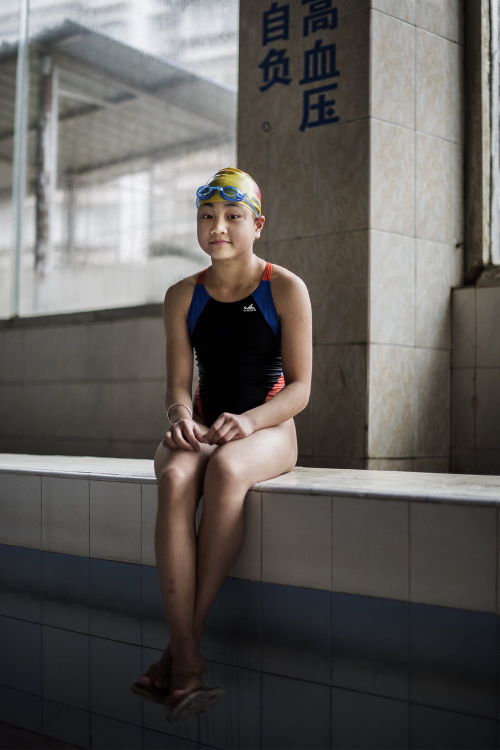 She has just finished one hour of intense training. Like a fish out of water her body shivers on the cold tiles. She closes her eyes and takes a deep breath, opens them and smiles calmly. Zou Jing (12) has attended South of the Clouds Swimming Club for one year.