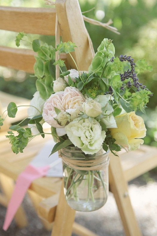 Use mason jars as aisle  markers. Just take some rope or wire    and make a handle and  hang them from shepherd's hooks. These would make great photos for the outdoor chic wedding.