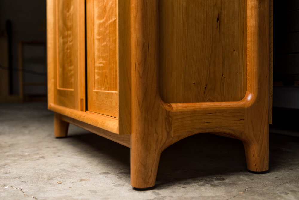 Credenza detail: Cabinet encased within leg frame