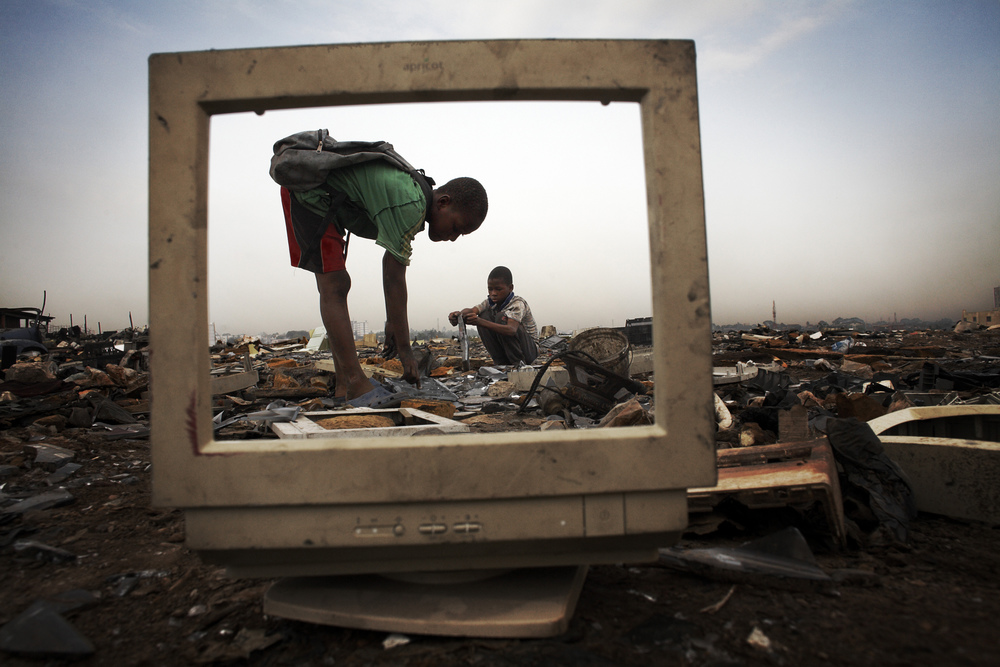 Chilrden extracting metal from e-waste landfill in Agbogbloshie, Ghana.