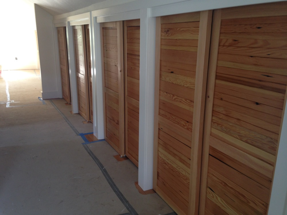 Master suite hallway storage and closet space with natural wood sliding doors.