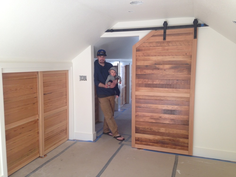 Morgan Holpuch, owner, and his son in the master suite checking on things after installation of master suite bedroom sliding barn door and closets.