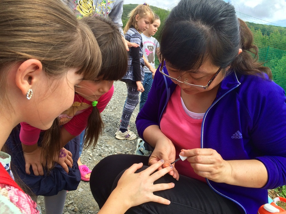 Our team member is getting busy with a part time job at the Camp. Nail painting during Free Time is a big hit for girls.