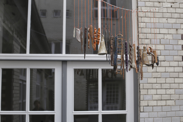 Kate Newby,  Let the thing in , 2013 ceramic wind chime, 26 elements