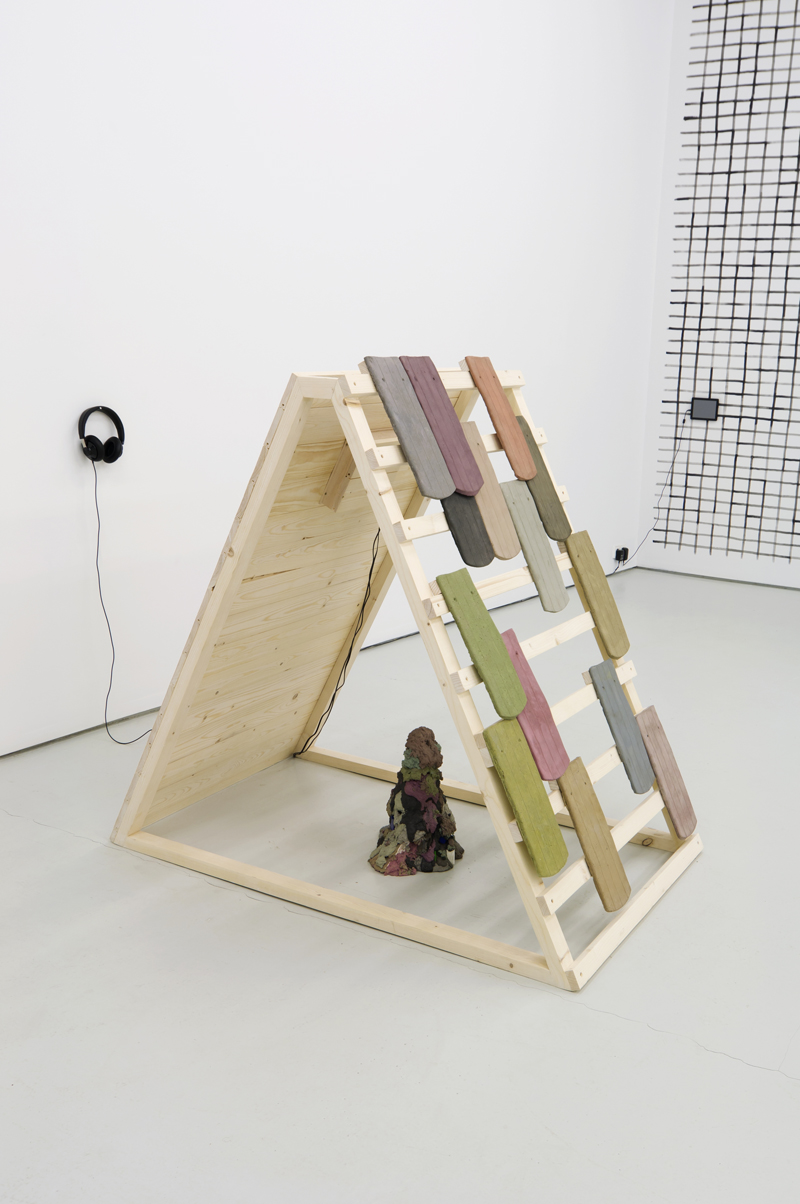 Katja Kollowa,  Mit Gunst und Verlaub (With favor and respect),  2012 installation / video (HD, 2.10 min.), wood, concrete, video screen, headphones, 1,37 x 1,49 x 0,92 cm