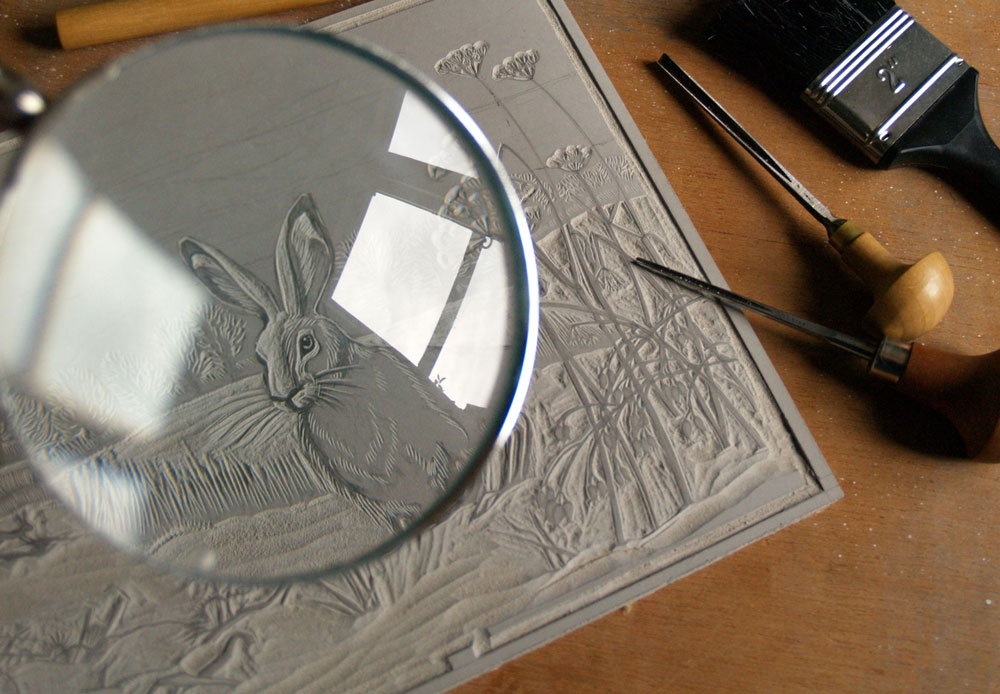 Niki Bowers highlighting the detail of her Winter Hares design carved into linoleum