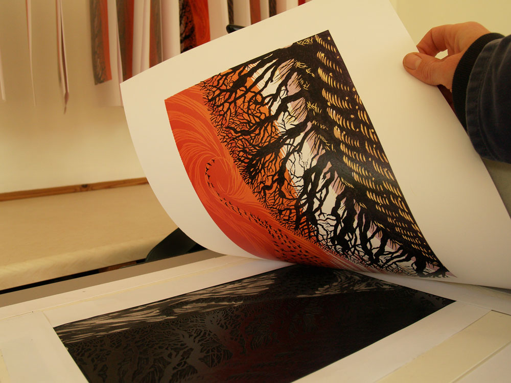 Niki Bowers pulling the finished Winter Starlings print off the inked up linoleum sheet