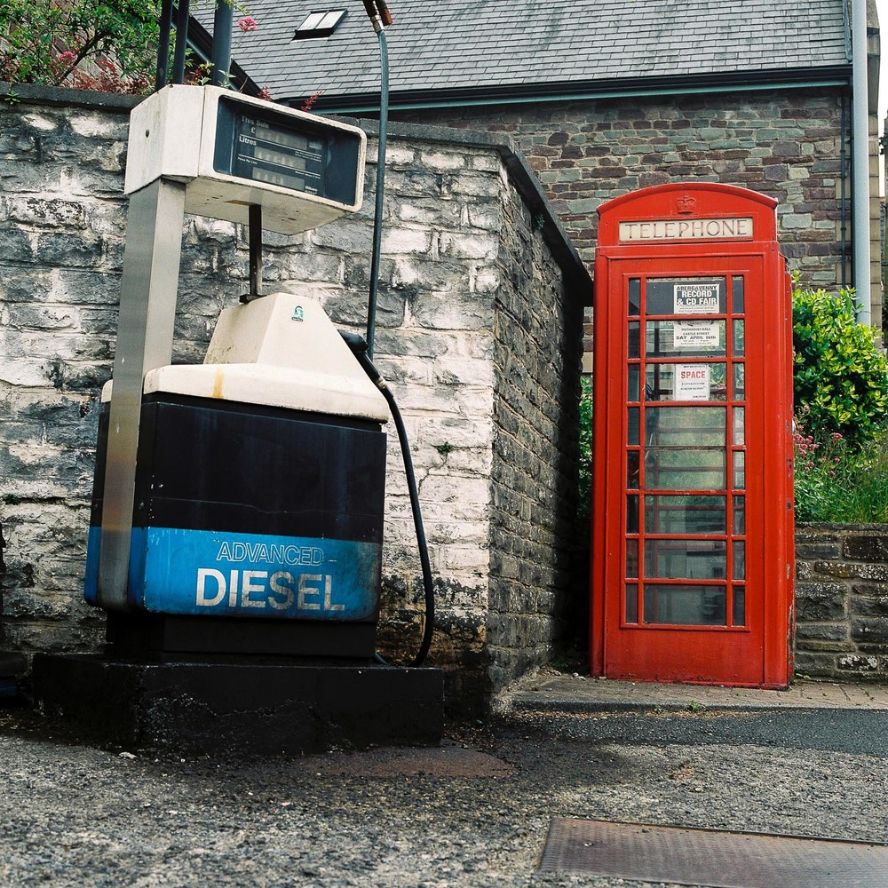An old diesel pump and a phone box next to each other, a typical scene in rural British town