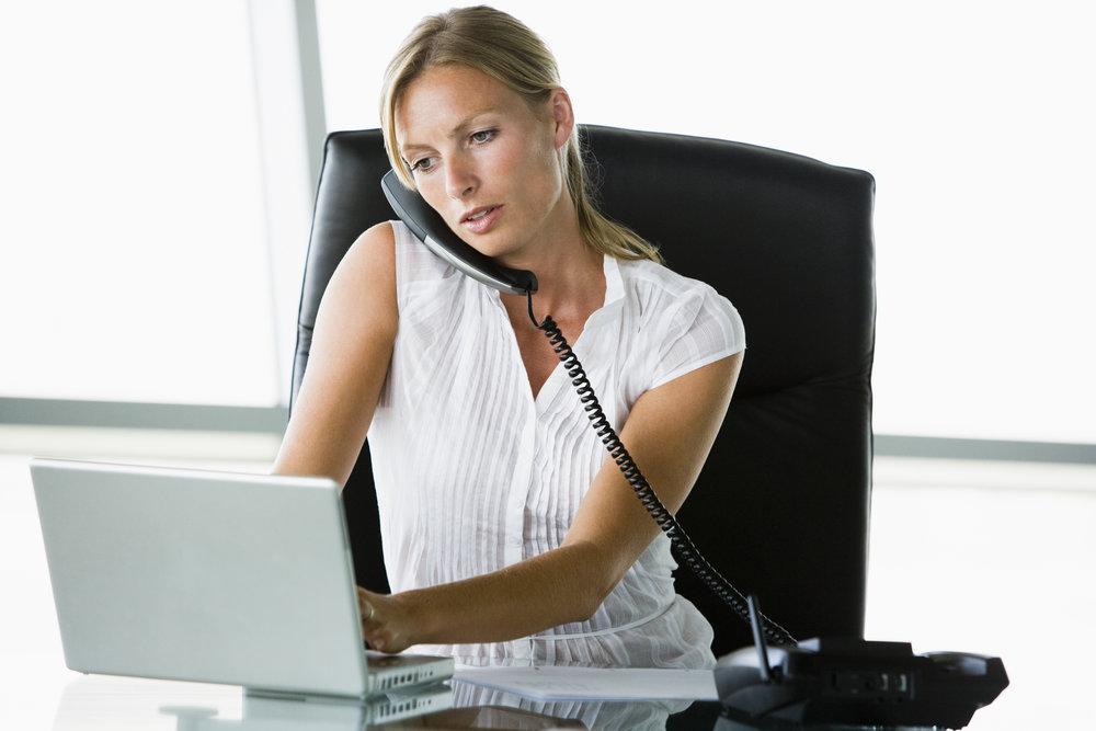 businesswoman-sitting-in-office-with-laptop-on-telephone_SFTqL6prj.jpg