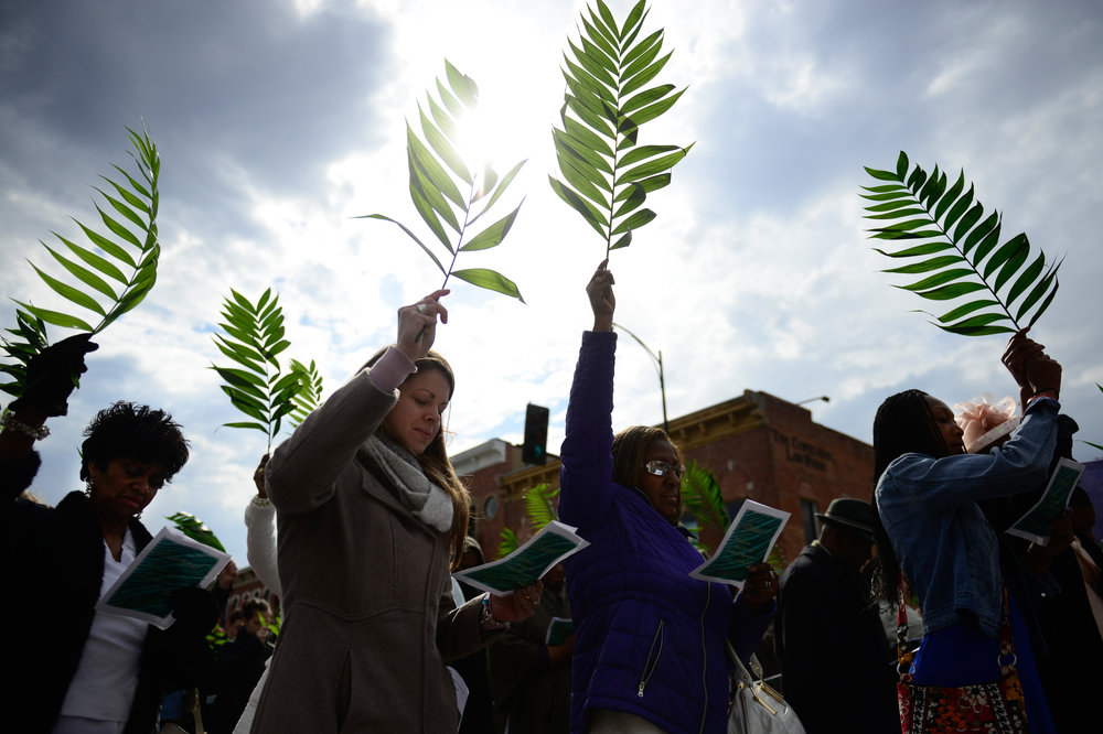 People raise their palm leaves during the Blessing of the Palms at the intersection of Ninth Street and Broadway in Columbia, MO, on Sunday, March 29. About nine churches from downtown Columbia participated in the event.