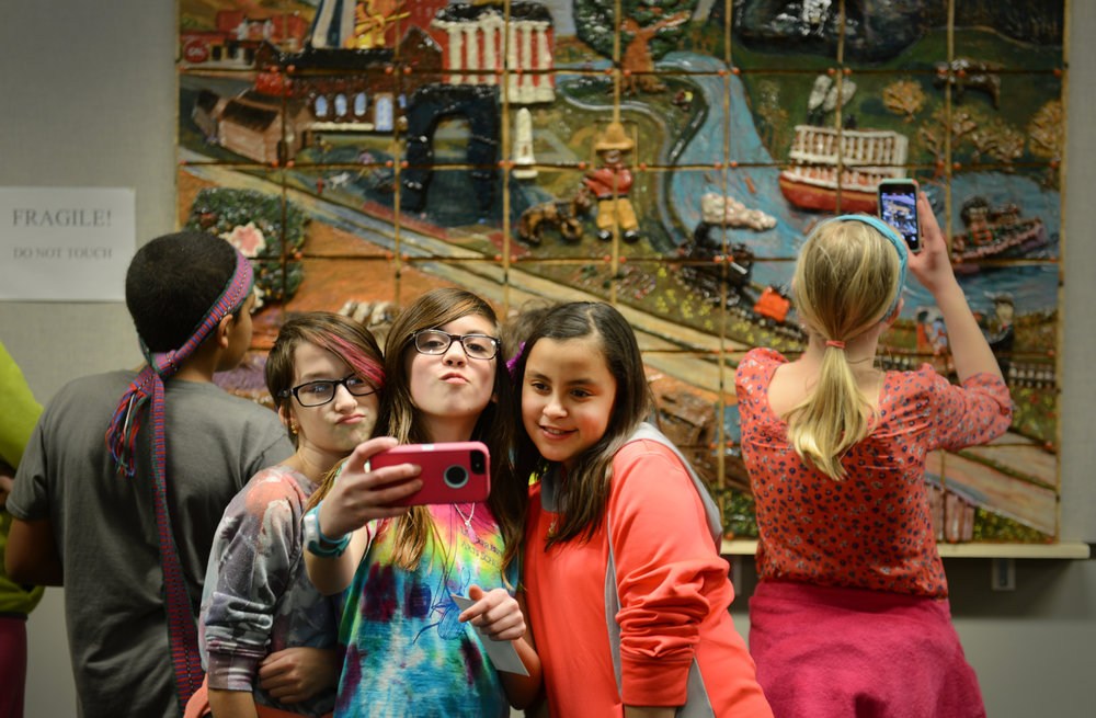 From left,Lee Expressive Arts Elementary students Devin Hall, left, 10, Ellie Bacon,11, and Keya Beamer, 10, take a selfie in front of the mural they helped create on Tuesday, March 3, 2015, in Columbia, MO. The fifth grade class at the elementary school made the mural for the State Historical Society.