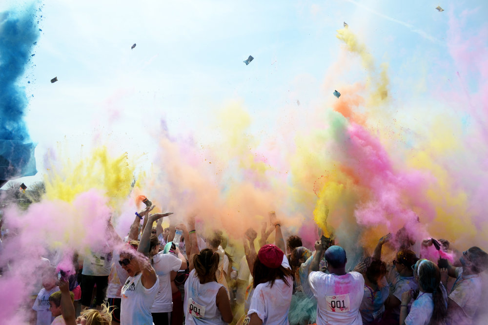 People celebrate with a 'color explosion' after completing the Color Dash 5K at Stephens Lake Park in Columbia, MO, on Saturday, April 6. Proceeds from the event went toward the local Humane Society.