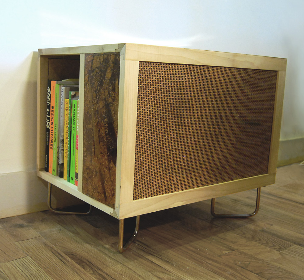 The Lucy Table contains a speaker in front, side shelving, custom joinery and cast resin/fiberboard composite.