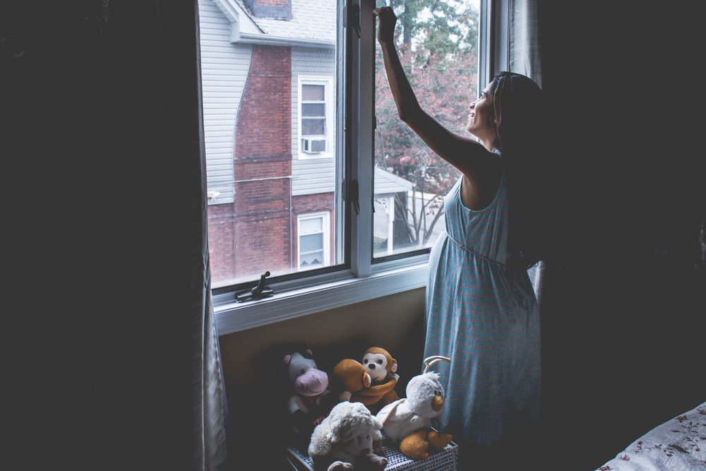 New Jersey Family Photographer - Pregnant woman looking out a window