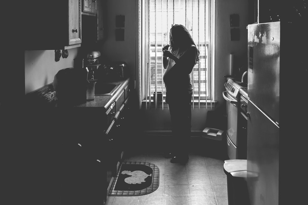 New Jersey Family Photographer - Black and white photo - Silhouette of Pregnant Woman Eating In Front of Kitchen Window