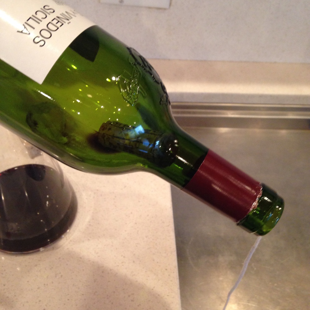 Step 5: Tilt the bottle in order to get the cork as close to the neck as possible. The knot should be behind the cork.