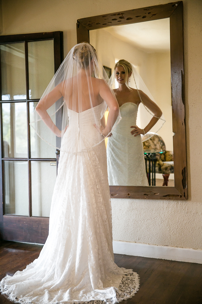bride looking on the mirror on a bridal dress
