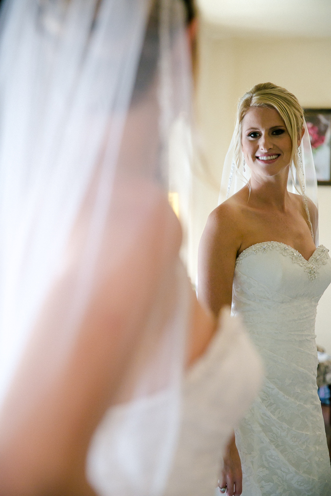 bride looking on the mirror with veil