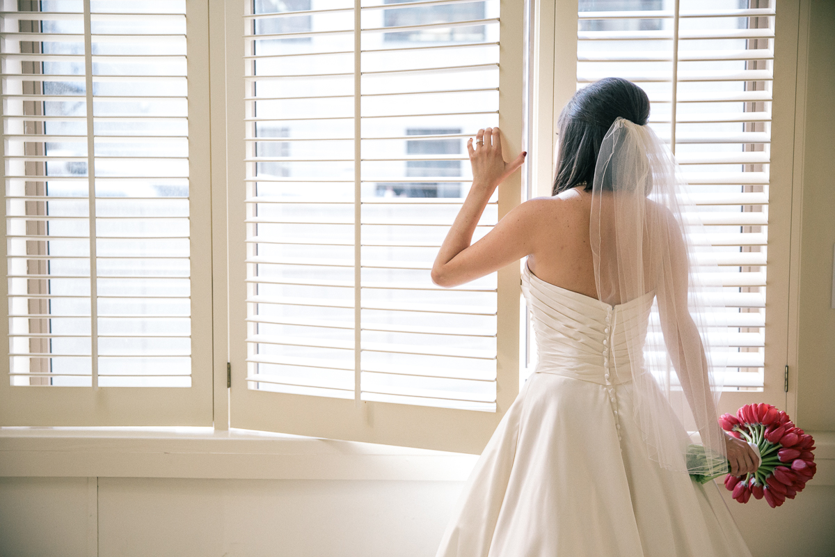 Bride picking out the window at Loft Seven Los Angeles, wedding Photograpjy