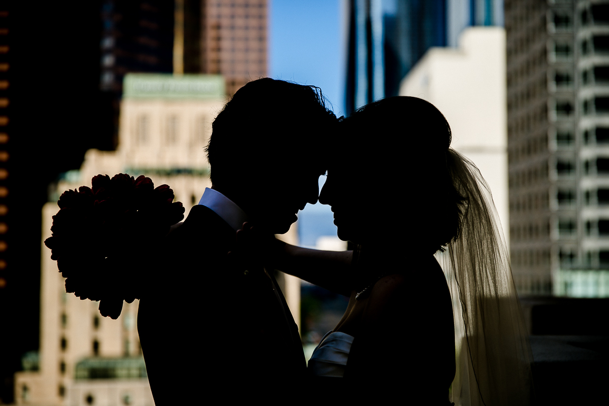 Bride and Groom overlooking downtown LA from the top of the Hilton Checkers Hotel at Loft Seven Los Angeles, wedding Photograpjy
