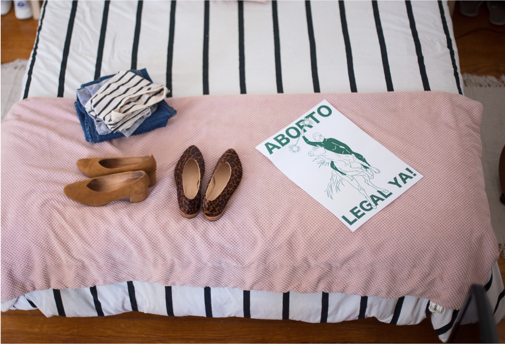 Above, a folded pile of Daiana's comfortable but stylish uniform of denim and tees; the ZX Belu Pump in a past season color and the Glove Flat in Leopard Pony; A poster Daiana designed + illustrated in the color green for Argentina's 'Legal Abortion Now' August 2018 march.