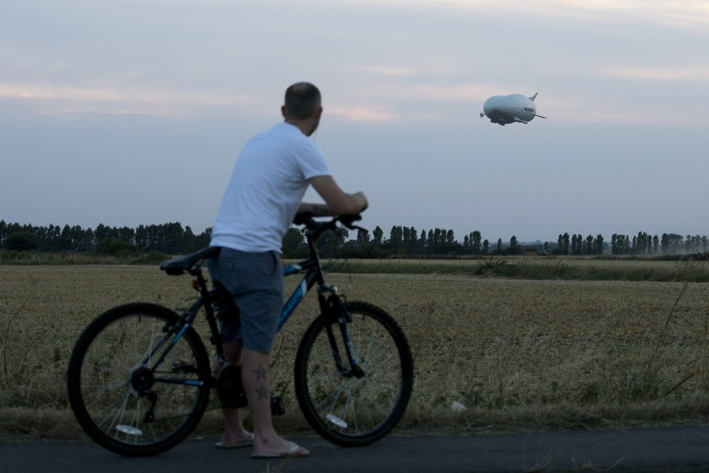 A cyclist stops to watch the Hybrid Air Vehicles HAV 304 Airlander 10 hybrid airship on its maiden flight from Cardington Airfield near Bedford, north of London, on August 17, 2016. © JUSTIN TALLIS / AFP