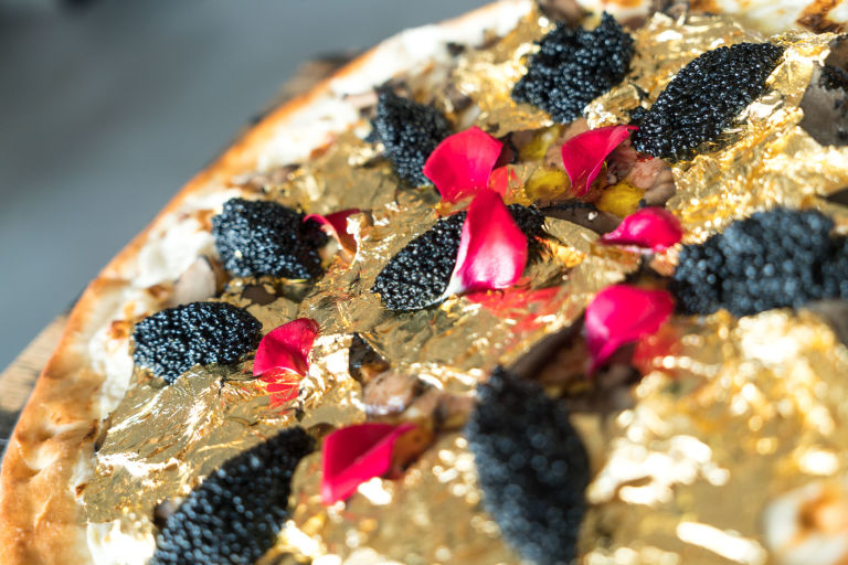 Industry Kitchen's golden pizza includes delicacies like Ossetra caviar and foie gras. Industry Kitchen