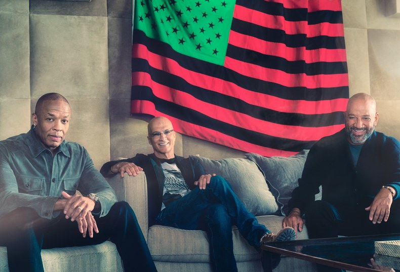Dr. Dre, Jimmy Iovine, and Allen Hughes, photographed at Iovine's house, with African-American Flag (1990), by David Hammons, in Los Angeles. Photograph by Kurt Iswarienko.