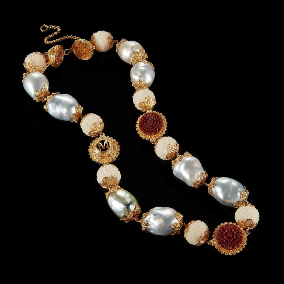 A necklace made of tagua seeds, baroque pearls and 22k gold beads with carved red wood lotus flower