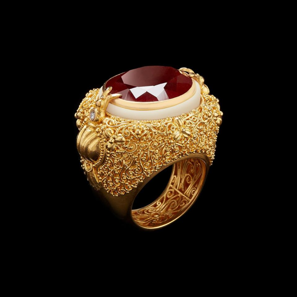A ring with an oval cut garnet, tagua, 22k gold wire work in a lace pattern and diamonds