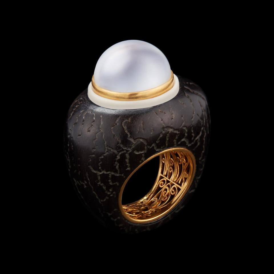 A ring with a pearl set on wood and tagua seed