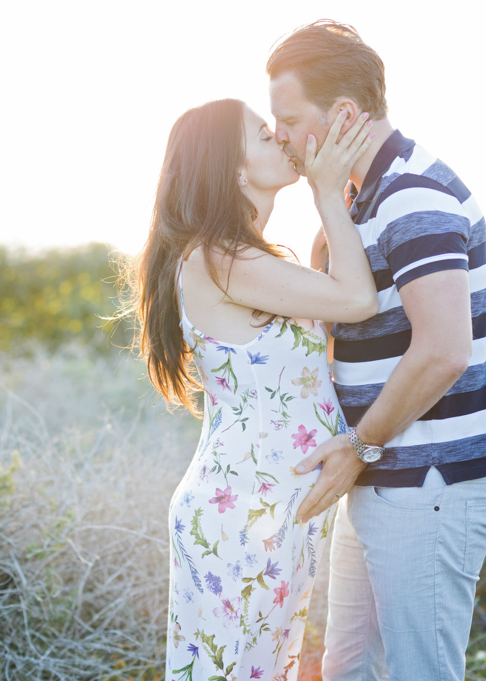 parents to be pregnant sunset backlight kissing happy people mountains close to sea malta maternity shoot maternity dress belly maternity bump